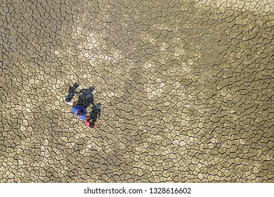Aerial top angle view of unrecognized woman with two kids walking side by side on crack soil during drought dry season at countryside in borneo.