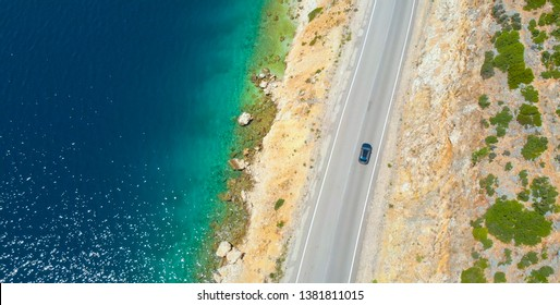 AERIAL, TOP DOWN: Car cruises down the empty asphalt road leading along the beautiful rocky beach in Lefkas. Flying above the coastline of an isle in the Mediterranean and car driving down scenic road