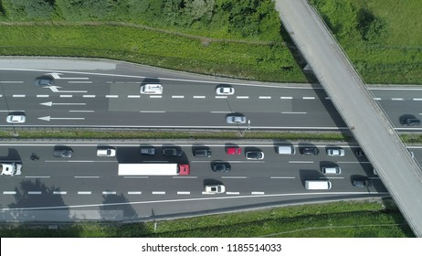 AERIAL, TOP DOWN: Cars and trucks drive through a congestion forming under the concrete overpass. Flying above the busy highway on a sunny day. Commuters and travelers driving up and down asphalt road