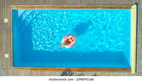 AERIAL, TOP DOWN: Cheerful young woman sunbathing while relaxing on a cool inflatable doughnut in her backyard pool. Smiling blonde haired girl in pink bikini lying on a funny floatie in amazing pool.