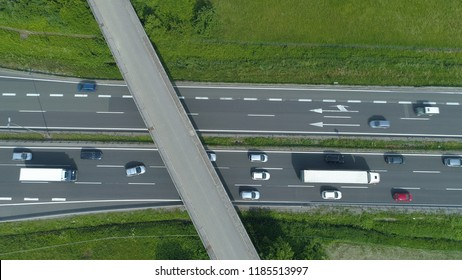 AERIAL, TOP DOWN: Colorful vehicles move along the busy freeway and under a concrete overpass. Flying above cars and trucks driving up and down a bustling highway running through the green nature.