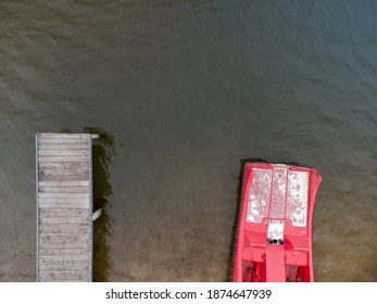 Aerial top down drone shot of wooden pier for swimmers and red paddleboat on the beach at lake of local recreation area