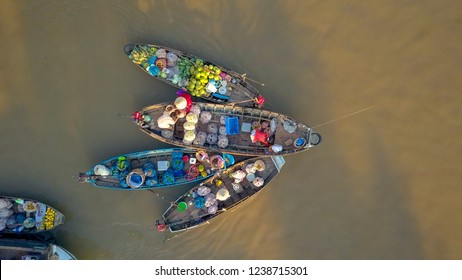 AERIAL, TOP DOWN: Flying away from bustling floating market on the tranquil river delta in the Vietnamese countryside. Local people offering their produce from their wooden boats on a sunny evening.