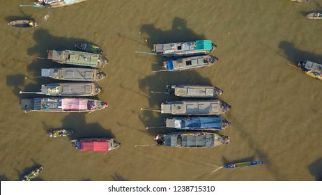 AERIAL, TOP DOWN: Flying over the wooden boats forming the famous floating market in sunny Vietnam. Longtail boat cruising past the idyllic Asian market set on the polluted river. Idyllic local life.