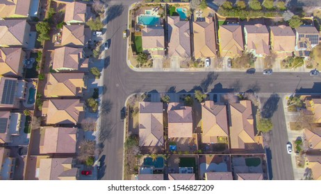 AERIAL TOP DOWN: Flying over terraced houses in a luxury suburban neighborhood in Nevada. Cinematic shot of row houses and backyards in the sunny suburbs of Las Vegas. Empty roads run through suburbia