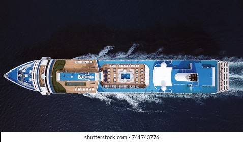 Aerial top down full view of luxury large cruise ship sailing full speed on open water, a top down view of swimming pool and deck