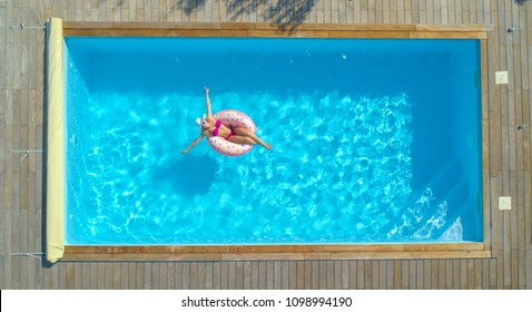 AERIAL, TOP DOWN: Happy Caucasian woman paddling around the crystal clear pool on her cool inflatable doughnut. Joyful female tourist relaxing on a funny floatie during a day off at a luxury pool.