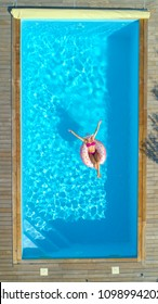 AERIAL, TOP DOWN: Joyful fit girl in pink swimsuit chilling on a doughnut floatie in the summer. Gorgeous Caucasian woman suntans while floating around the crystal clear pool on inflatable doughnut.
