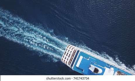 Aerial top down of luxury large cruise ship sailing full speed on open water, a top down view of swimming pool and deck
