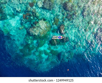 Aerial top down people snorkeling on coral reef tropical caribbean sea, turquoise blue water. Indonesia Indonesia Moluccas archipelago, Banda Islands, Pulau Hatta, tourist diving travel destination