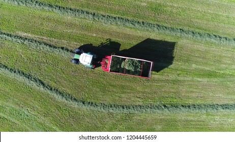 Aerial top down photo of chaser bin also called grain cart or auger wagon is trailer towed by tractor with a built-in conveyor system used for pickup of dried crops from land in this case grass