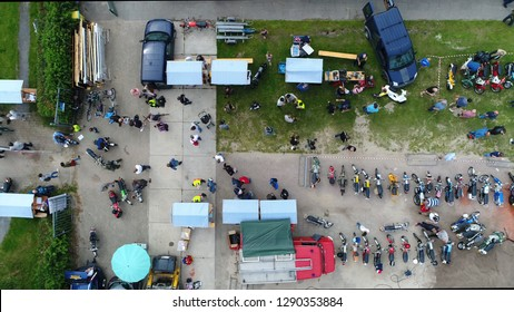 Aerial top down photo of classic motorcylce event festival terrain with old bikes and mopeds parked and visitors walking over the field also showing stalls and vintage fire truck