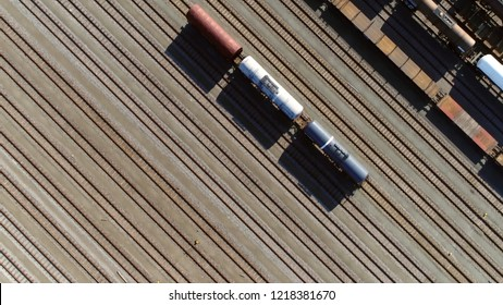 Aerial top down photo of classification yard with goods wagons on the railroad gathering found at some freight train stations used to separate rail cars onto one of several tracks
