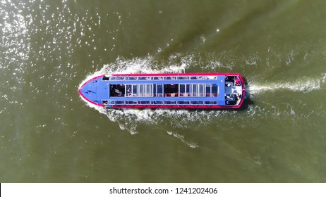 Aerial top down photo of electric canal cruise boat with sliding panel glass roof moving over IJ this is one of most popular tourist activities done in Amsterdam Netherlands