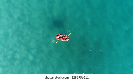 Aerial top down photo of inflatable toy boat with two kids rowing over shallow azure blue lagoon crystal clear water typical tropical vacation scene footage of ocean