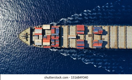 Aerial top down photo of large cargo container ship cruising the deep blue Mediterranean sea