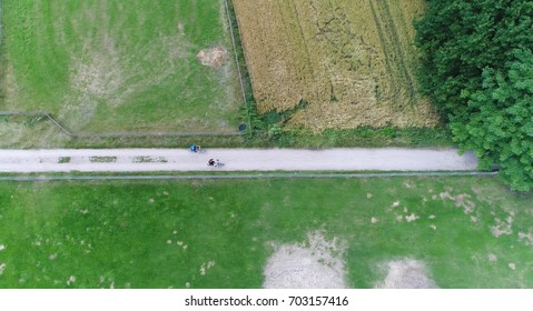 Aerial top down photo of rural area above bike path two cyclists drive past over this rural bikeway