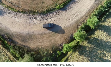 Aerial top down photo of sport utility vehicle SUV driving over off-road gravel surface advanced vehicle equipped with raised ground clearance and four-wheel drive to support countryside unpaved roads