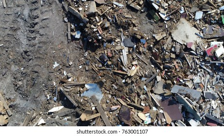 Aerial top down photo of tracks and landfill site also known as tip dump rubbish dump garbage dump or dumping ground site for disposal of waste materials by burial and oldest form of waste treatment