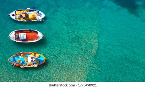 Aerial top down photo of traditional wooden fishing boat anchored near picturesque port of Spetses island, Saronic gulf, Greece