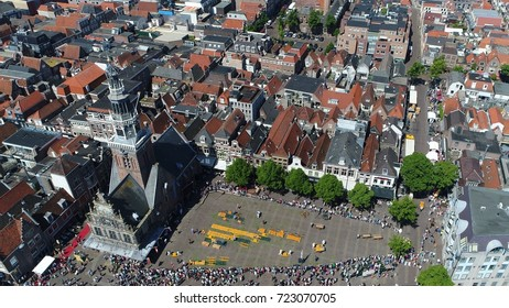 Aerial top down photo of traditional cheese market at Waagplein Alkmaar showing cheese merchants walking with trays of Alkmaar cheese towards next buyer this is popular tourist attraction Netherlands