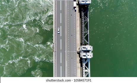 Aerial top down picture Eastern Scheldt storm surge barrier and vehicle driving over road in Dutch Oosterscheldekering the largest of 13 ambitious Delta Works series of dams and storm surge barriers