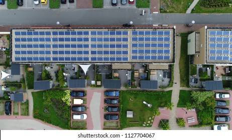 Aerial top down picture of newly built apartment complex with photovoltaic solar panels installed they absorb sunlight as source of energy to generate electricity in this residential application