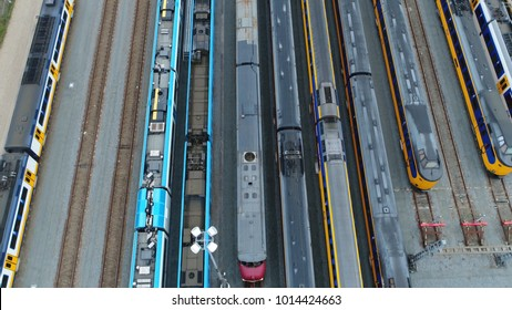 Aerial top down picture of railway hub and parked passenger trains next to each other moving slowly over the rail vehicles with different colors beautiful rail network