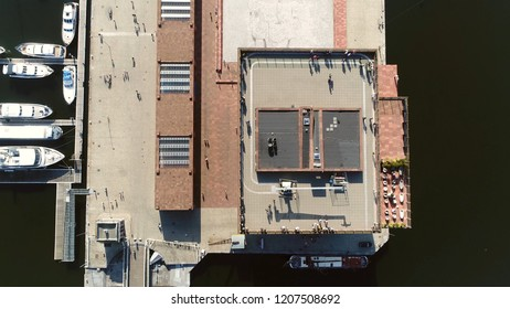 Aerial top down picture tall building roof in Belgium Antwerp located along the river Scheldt in Eilandje district showing people enjoying the beautiful weather of summer day