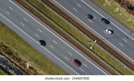 Aerial top down picture three lane major highway traffic driving in both ways showing vehicles on all lanes stabilized camera moving over the roads in evenly way