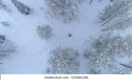 AERIAL, TOP DOWN: Unrecognizable person in bright green jacket walking through the snowy forest in rural Scandinavia. Flying above unknown tourist on a relaxing walk through the woods in Finland.