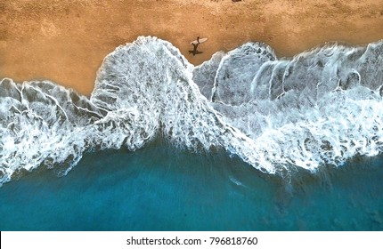 AERIAL, TOP DOWN: Unrecognizable surfer walking along the exotic sandy beach on sunny summer day. Lonely man holding surfboard looking at splashing ocean waves. Splashing ocean waves reach sandy beach