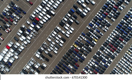 Aerial top down view above car lot with new vehicles ready for transportation