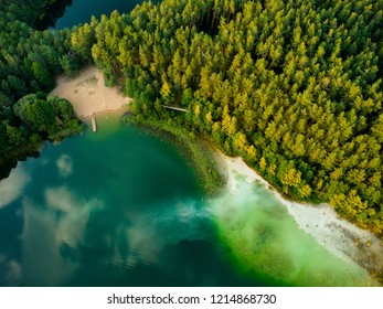 Aerial top down view of beautiful green waters of lake Gela. Birds eye view of scenic emerald lake surrounded by pine forests. Clouds reflecting in Gela lake, near Vilnius city, Lithuania.