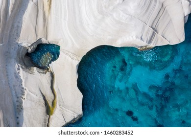 Aerial top down view to the chalk rock formations of Sarakiniko with sparkling blue sea, Milos island, Cyclades, Greece