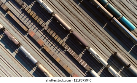 Aerial top down view of classification yard with goods wagons on the railroad gathering found at some freight train stations used to separate rail cars onto one of several tracks