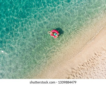 Aerial top down view of cute young girl floating on toy ring at Myrtos beach, the most beautiful beach of Kefalonia, a large coast with turqoise water and white coarse sand. Cephalonia, Greece.