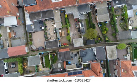 Aerial top down view flying over city showing neighborhood family houses real estate with orange red roofs and gardens