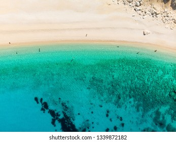 Aerial top down view of Myrtos beach, the most famous and beautiful beach of Kefalonia, a large coast with turqoise water and white coarse sand, surrounded by steep cliffs. Cephalonia, Greece.