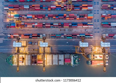 Aerial top down view over industry commercial port in Bangkok Thailand with big freight vessel loading product container at night. Shot by 4K resolution drone camera.