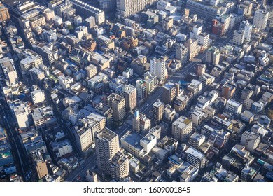 An aerial, top down view photo of a sea of colorful buildings in bright sunlight in central Tokyo, Japan.