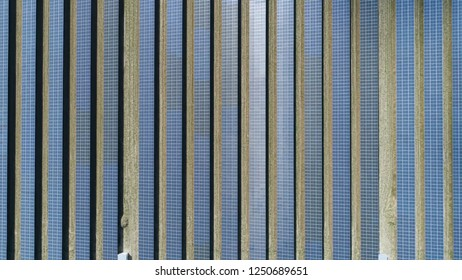 Aerial top down view of photovoltaic station also known as a solar park is large-scale PV system designed for supply of merchant power into the electricity grid by sunlight energy 4k high resolution