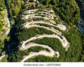 Aerial top down view of serpentine narrow road leading to Vikos Gorge in Northern Greece. A road full of twists and turns winding sharply up the mountain in Zagori region, Greece.
