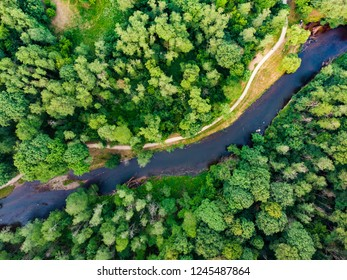 Aerial top down view of summer forest with narrow Vilnele river winding among the trees. Beautiful woods scenery near Vilnius city, Lithuania