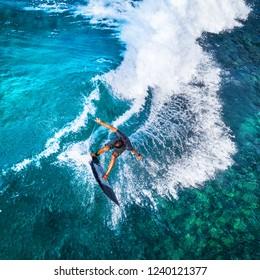 Aerial top down view of the surfer riding furious ocean wave. Makaha surf spot, Oahu, Hawaii