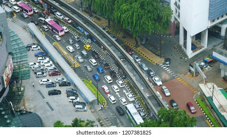 Aerial top down view of traffic jam on the road and walking people during rain