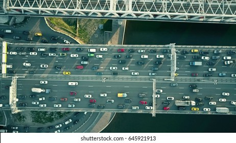 Aerial top down view of traffic jam on a car bridge and moving train