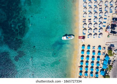 Aerial top down view to the umbrellas and the turquoise sea at the popular beach of Ornos, Mykonos island, Greece - Shutterstock ID 1865727334