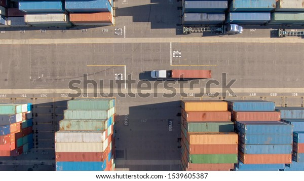 AERIAL, TOP DOWN: White truck transports a red freight container across the busy port of Los Angeles. Flying above a freight truck hauling a heavy shipment past large stacks of other containers.