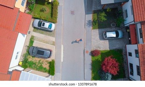 AERIAL TOP DOWN: Young couple going for energizing jog through the idyllic suburban neighborhood. Athletic man and woman running down an empty road leading through the middle class terraced house town